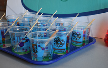 Mad science branded cups with popsicle sticks inside