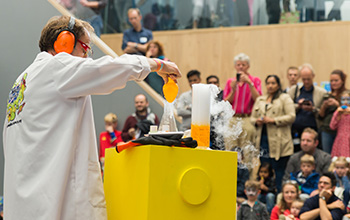 Mad scientist on stage in front of yellow podium with a beaker full of yellow liquid and smoke