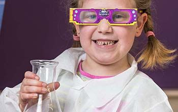 Girl smiling in Mad science lab coat holding a beaker wearing purple diffraction glasses