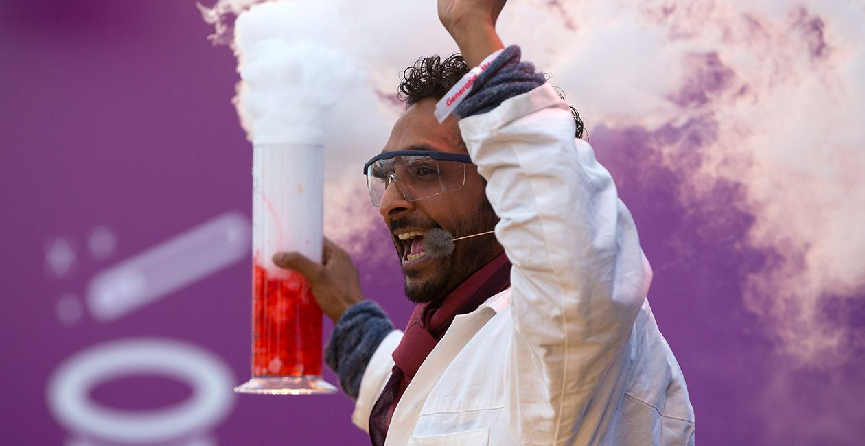 Mad scientist with hands in the air and microphone holding a beaker with a red liquid and smoke pouring out
