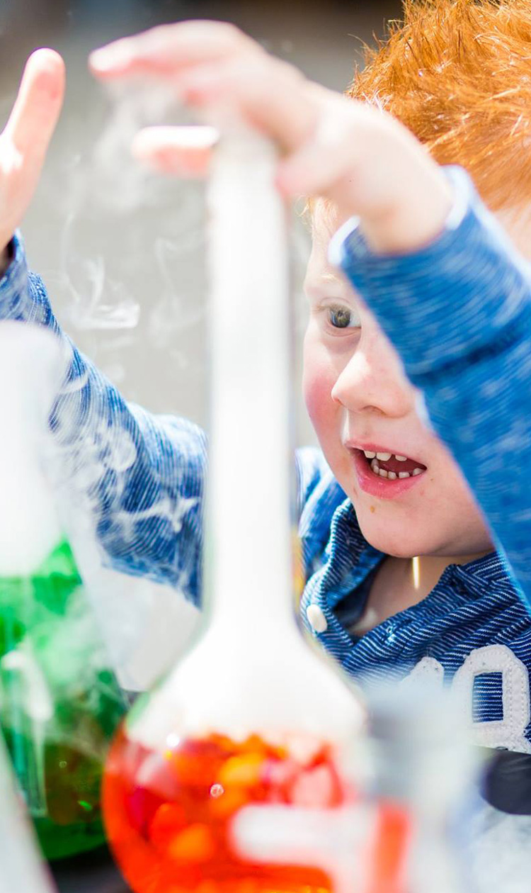 Boy playing with beakers with red and green liquid inside and smoke pouring out