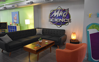 A mad science waiting area with couch, table chair and a mad science logo on the wall